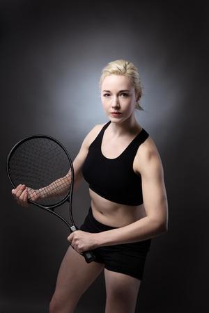 low key lighting: studio shot of woman holding a tennis racket on gray background low key lighting