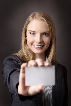 smartly: Close up image of a smartly dressed business woman holding a blank business card out infornt of her.  Part of the image is blurred.  Shot on a grey background