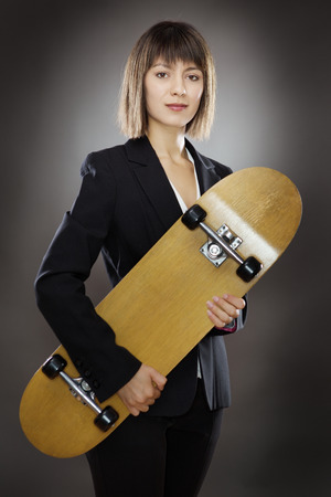 low key lighting: professional looking business woman holding a skateboard shot in the studio on a gray background low key lighting Stock Photo