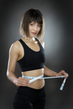 low key lighting: low key lighting of a woman using a tape measure around her waist