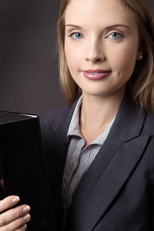 file box: Close up upper body shot of a smiling business model, holding a black box file. Shot on a grey background. Stock Photo
