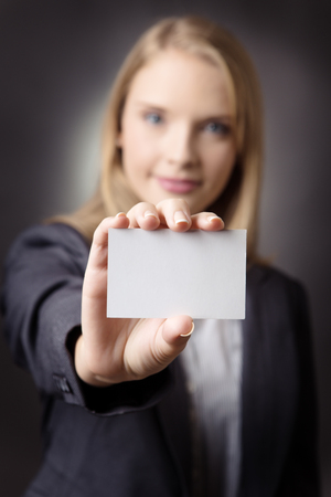 smartly: Close up image of a smartly dressed business woman holding a blank business card out infornt of her.  Part of the image is blurred. Stock Photo