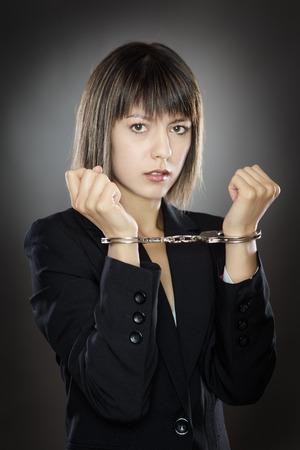 encerrado mujer de negocios con las manos esposadas con las manos arriba