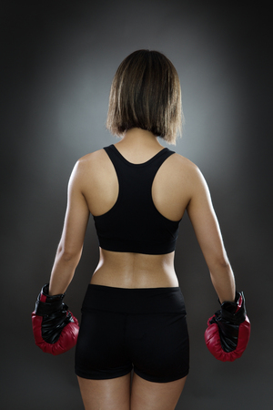 low key lighting: low key lighting of a womans from the back wearing boxing gloves shot in the studio on a gray background