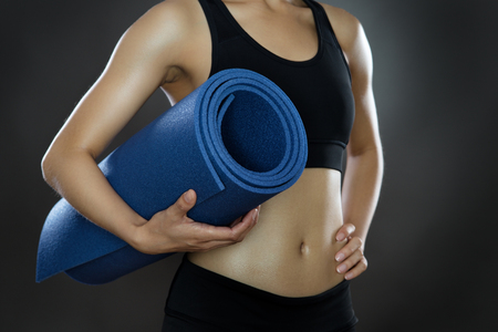 low key lighting: close up shot with low key lighting of a womans midriff holding a sports mat shot in the studio on a gray background Stock Photo