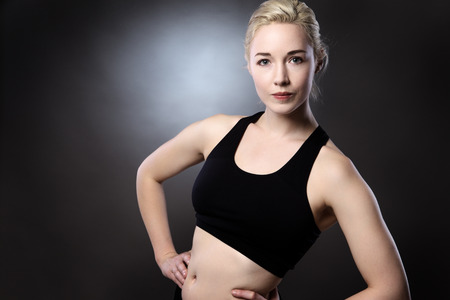 low key lighting: athletic woman shot in the studio low key lighting on gray background