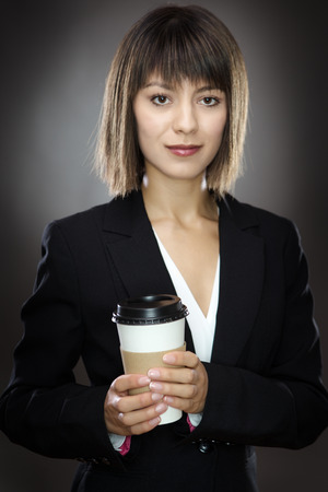 sharply: portrait of young sharply dressed business woman holding a take away cup shot in the studio low key lighting on a gray background Stock Photo