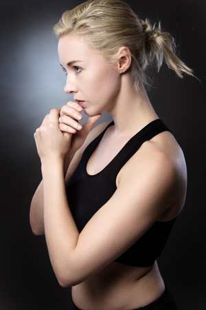 low key lighting: fitness woman concentrating hard shot in the studio low key lighting