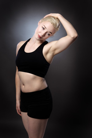 low key lighting: stretching athlete woman shot in the studio low key lighting on gray background Stock Photo