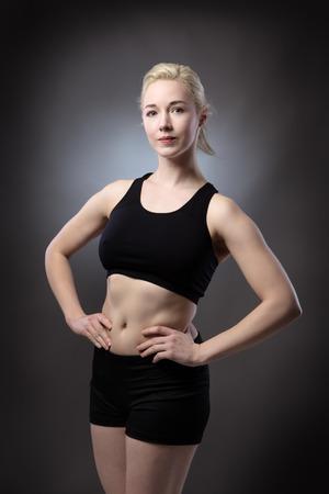 low key lighting: fitness woman shot in the studio low key lighting on gray background