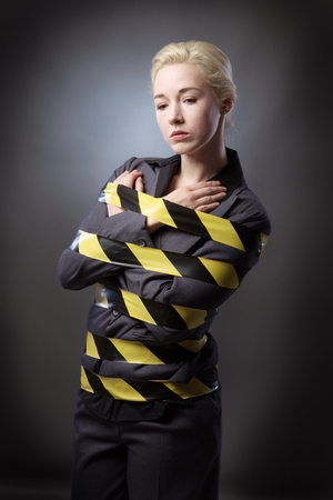 stuck up: Business woman wrapped up in yellow and black tape, shot on a grey background. Stock Photo
