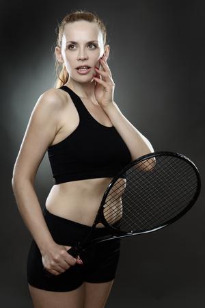 low key lighting: fitness woman holding a tennis racket shot in the studio low key lighting