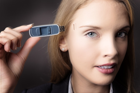 memory stick: Close-up head shot of a business woman holding a memory stick to the side of her head Stock Photo