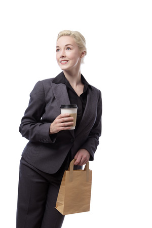 Studio shot of a pretty business woman holding a brown paper bag
