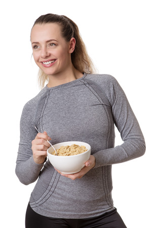 comiendo cereal: happy woman wearing fitness clothes eating cereal