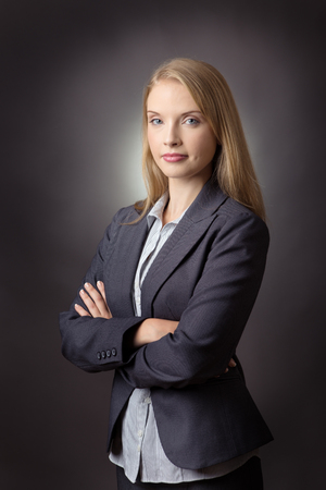 cross armed: Close up image of a business woman with arms folded. shot on a grey background.
