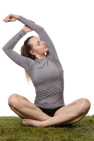 relaxed woman wearing fitness clothes sitting cross legged on grass stretching her arms
