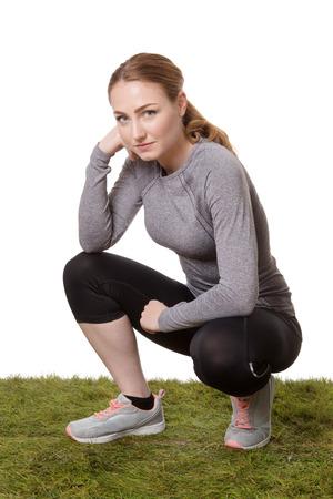 mujer arrodillada: fitness mujer de rodillas sobre la hierba