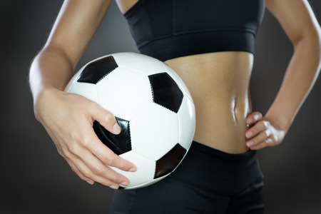 midriff: close up shot of a womans midriff holding a football shot in the studio on a gray background