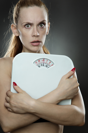 low key lighting: woman shot in the studio, low key lighting holding weight scales close to her chest looking worried Stock Photo