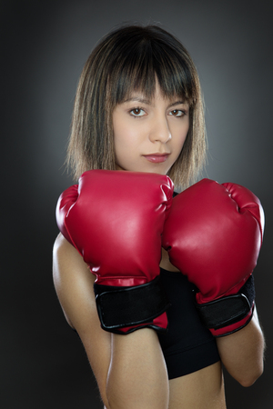 low key lighting: low key lighting of a woman wearing boxing gloves shot in the studio on a gray background