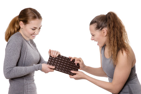 pull over: two women wearing fitness clothes fighting over chocolate