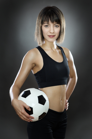 low key lighting: low key lighting of a woman holding a english football shot in the studio on a gray background