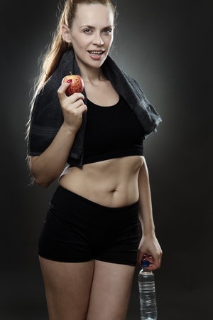 low key lighting: fitness woman chilling out after a long workout shot in the studio on a gray background low key lighting set up Stock Photo