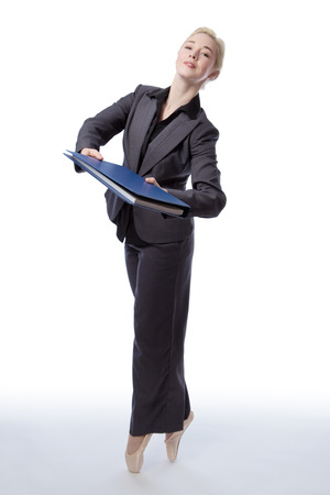poised: Studio shot of a pretty blonde business model, wearing a suit and ballet shoes, is enpointe whilst holding a blue folder, isolated on a white background. Stock Photo