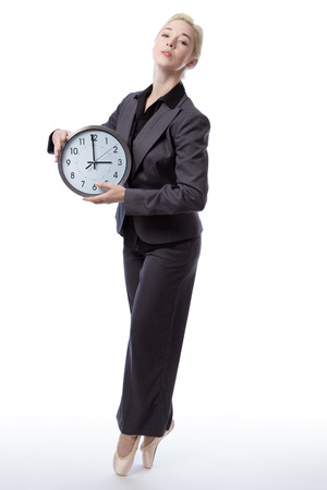 analogue: Studio shot of a pretty blonde business model, wearing a suit and ballet shoes, is enpointe whilst holding a large analogue clock showing the time, isolated on a white background.