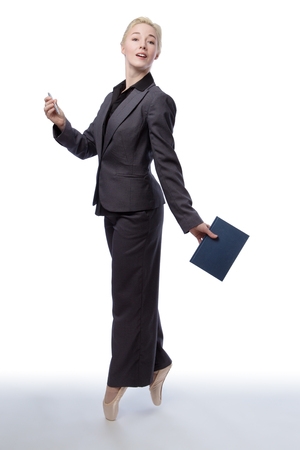closed book: Studio shot of a pretty blonde business model, wearing a suit and ballet shoes, is enpointe whilst holding a closed book in one hand, isolated on a white background. Stock Photo