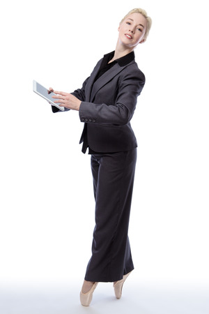 en pointe: Studio shot of a pretty blonde business model, wearing a suit and ballet shoes, is enpointe whilst holding a tablet computer, isolated on a white background.