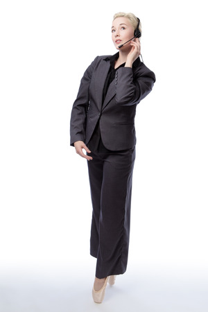 whilst: Full length studio shot of a pretty blonde business model, wearing a suit and ballet shoes, is enpointe whilst wearing a headset, isolated on a white background. Stock Photo