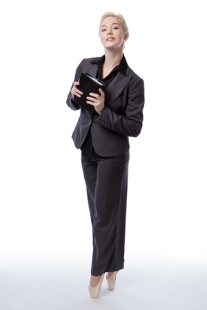 en pointe: Full length shot of a business ballerina holding a little black book, whilst en-pointe.  Isolated on white Stock Photo
