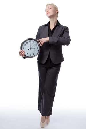 poised: Studio shot of a pretty blonde business model, wearing a suit and ballet shoes, is enpointe whilst holding a large analogue clock showing the time, isolated on a white background.