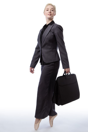 poised: Studio shot of a pretty blonde business model, wearing a suit and ballet shoes, is enpointe whilst holding a briefcase, isolated on a white background.
