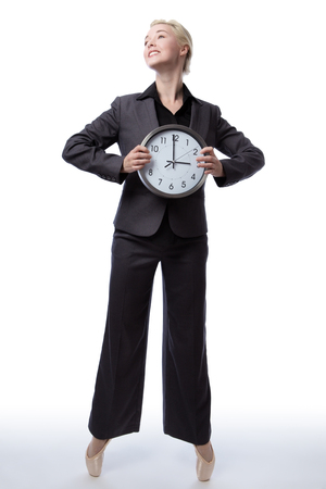 poised: Studio shot of a pretty blonde business model, wearing a suit and ballet shoes, is enpointe whilst holding a large analogue clock showing the time.