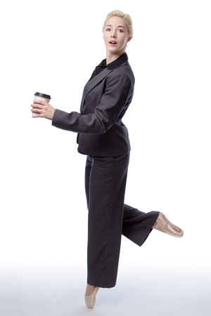 en pointe: Studio shot of a pretty blonde business model, wearing a suit and ballet shoes, is enpointe whilst holding a takeaway drink, isolated on a white background. Stock Photo