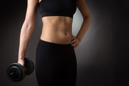 midriff: Close-up shot of the torso of a female dressed in fitness wear, holding a hand weight,with the other hand on her hip, facing the camera. Stock Photo