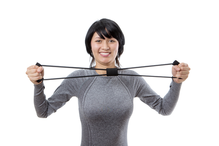 elastic band: Upper body studio shot of a pretty, young fitness model exercising using a resistance elastic band.