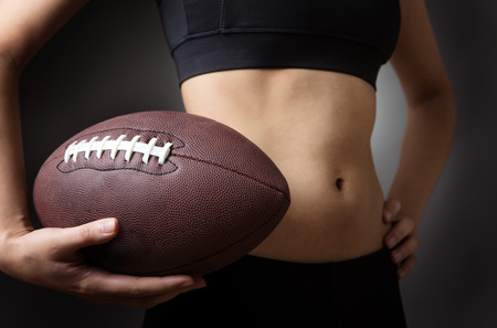 midriff: Close up shot of a slim young models abdomen, whilst holding a american football close to her abdomen. Low key lighting shot on a grey background