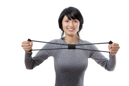 Upper body studio shot of a pretty, young fitness model exercising using a resistance elastic band.