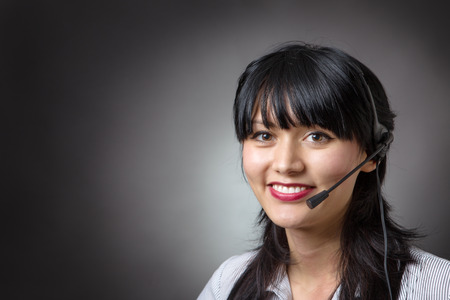 telemarketer: female call center assistant or telemarketer wearing a headset looking at the camera with a charming friendly smile, shot on a grey background.