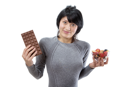 decide: fitness model wearing a grey long sleeved top, trying to decide between a big bar of chocolate and a fruit salad.