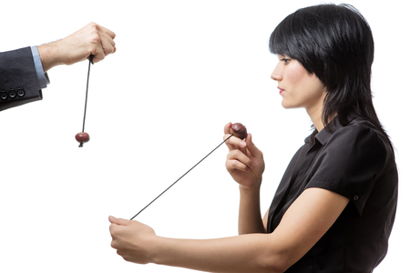 conkers: Studio shot of male and female business co-workers having a game of conkers, isolated on white. Stock Photo