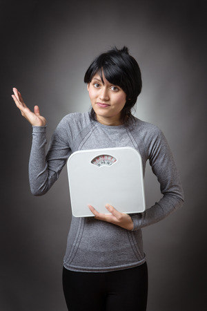 low key lighting: attractive fitness model, holding scales, looking confused about her weight. low key lighting shot on a grey background. Stock Photo