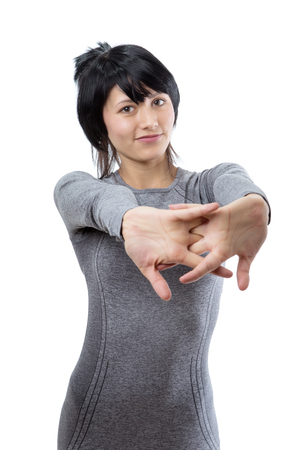 upper body: Upper body shot of a slim young female fitness model, wearing a long sleeved grey top, with her hands clasped infront of her, stretching.