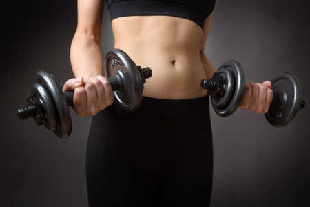 midriff: Close up shot of a very slim fitness model weightlifting dumbells.  low key lighting shot on a grey background Stock Photo
