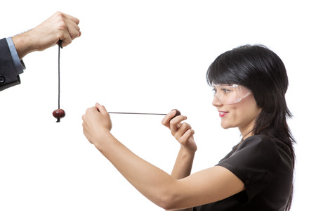 conkers: Studio shot of a business female wearing protective  playing conkers Stock Photo