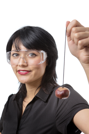 conkers: Studio shot of a business female wearing protective glasses ready to play conkers Stock Photo